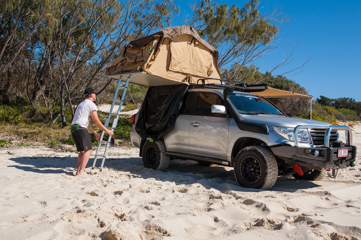 Climbing up the ladder to get into the Ironman 4x4 rooftop tent & ironman-4x4-rooftop-tent-climbing-up-ladder | 4x4 Accessories Online