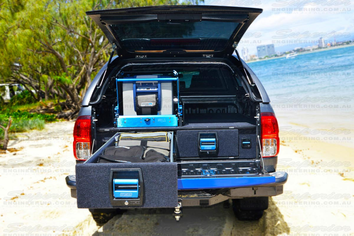 Rear view a Hilux with the MSA 4x4 draw system complete with one draw open and one draw closed with a fridge and drop slide