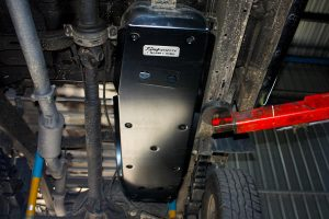 A closeup under vehicle view of the Superior Engineering aftermarket fuel tank guard which has been fitted to the Ford Ranger which fully covers the fuel tank and perfectly integrates into the vehicle design